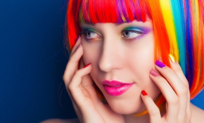 stock-photo-beautiful-woman-wearing-colorful-wig-and-showing-colorful-nails-against-blue-background-228344581