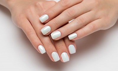 Wedding white pearl manicure on short square nails on a white background close-up.